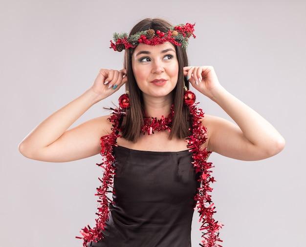 Erfreut junges hübsches kaukasisches mädchen mit weihnachtskopfkranz und lametta-girlande um den hals hängende weihnachtskugeln an den ohren, die auf die seite isoliert auf weißem hintergrund schauen