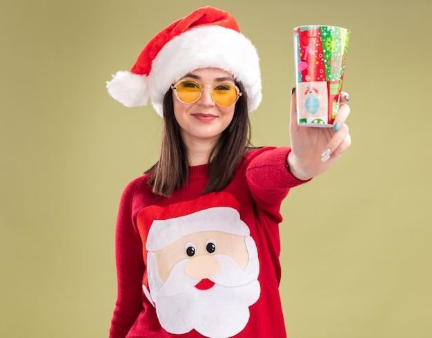 Erfreut junges hübsches kaukasisches mädchen mit weihnachtsmann-pullover und -hut mit brille, das plastikweihnachtsbecher in richtung kamera ausstreckt und die kamera einzeln auf olivgrünem hintergrund betrachtet