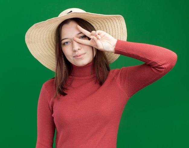 Erfreut junges hübsches mädchen mit strandhut, das ein v-zeichen-symbol in der nähe des auges zeigt