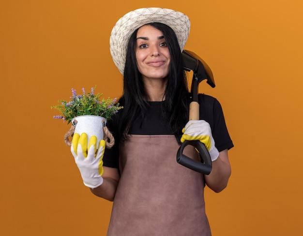 Erfreut junges kaukasisches gärtnermädchen, das uniform und hut mit gärtnerhandschuhen trägt, die spaten und blumentopf isoliert auf oranger wand halten