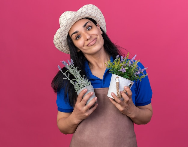 Erfreut junges kaukasisches gärtnermädchen in uniform und hut, das blumentöpfe isoliert auf rosa wand mit kopienraum hält