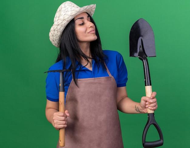 Erfreut junges kaukasisches gärtnermädchen in uniform und hut, das rechen und spaten hält und auf spaten schaut