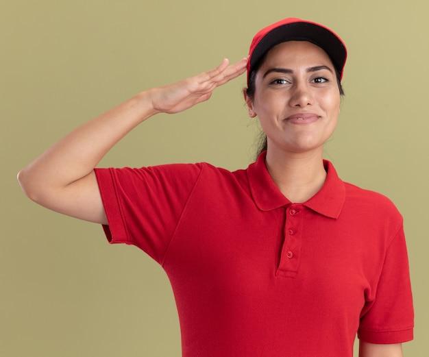 Erfreut junges liefermädchen, das uniform mit mütze trägt und grußgeste zeigt, isoliert auf olivgrüner wand