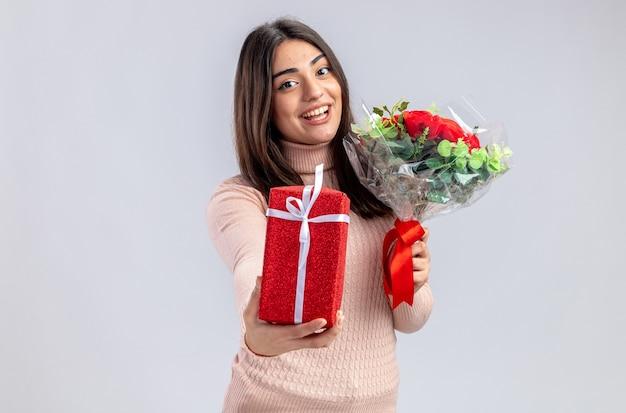 Erfreut junges mädchen am valentinstag mit geschenkbox mit blumenstrauß isoliert auf weißem hintergrund