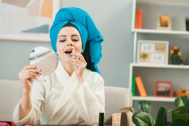 Erfreut junges mädchen, das haare in ein handtuch wickelt, das lippenstift hält und den spiegel betrachtet, der am tisch mit make-up-tools im wohnzimmer sitzt?