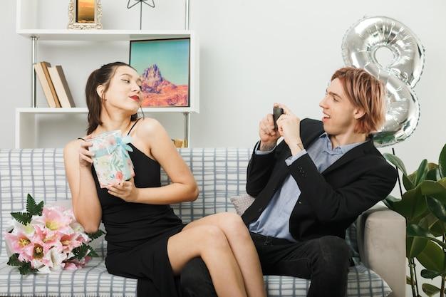 Erfreut junges paar am glücklichen frauentag mädchen, das den anwesenden kerl hält, machen ein foto, das auf dem sofa im wohnzimmer sitzt