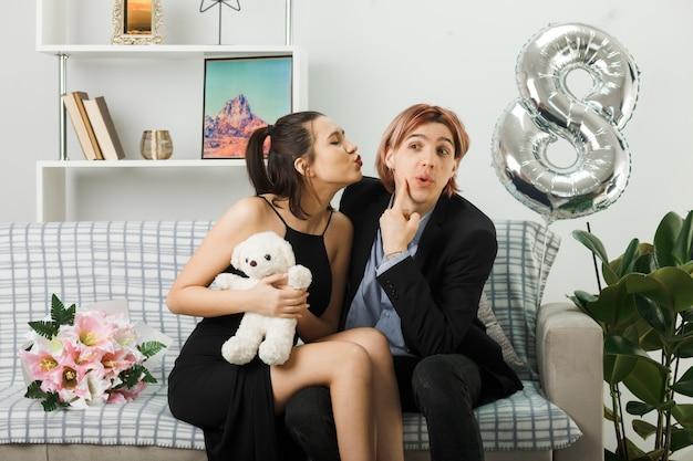 Erfreut junges paar am glücklichen frauentag mit teddybärmädchen, das seine wange küsst und auf dem sofa im wohnzimmer sitzt