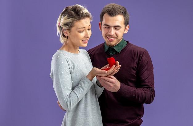Erfreut junges paar am valentinstag mit blick auf ehering in mädchenhänden isoliert auf blauem hintergrund