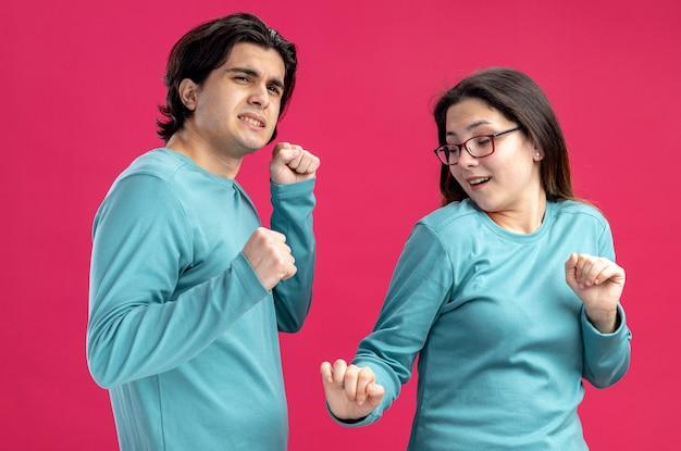Erfreut junges paar am valentinstag tanzen isoliert auf rosa hintergrund