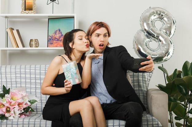 Erfreut, junges paar mit kussgeste am glücklichen frauentag mit geschenk zu zeigen, machen sie ein selfie, das auf dem sofa im wohnzimmer sitzt
