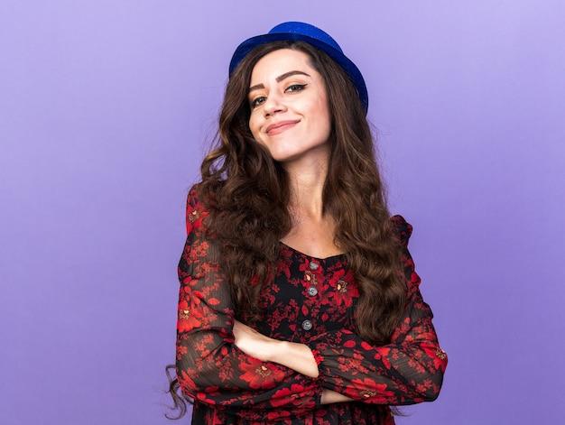 Erfreut junges partygirl mit partyhut, das mit geschlossener haltung isoliert auf lila wand mit kopienraum steht