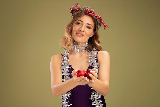 Erfreut junges schönes mädchen, das lila kleid und kranz mit girlande am hals trägt, die weihnachtsbaumkugeln einzeln auf olivgrünem hintergrund hält