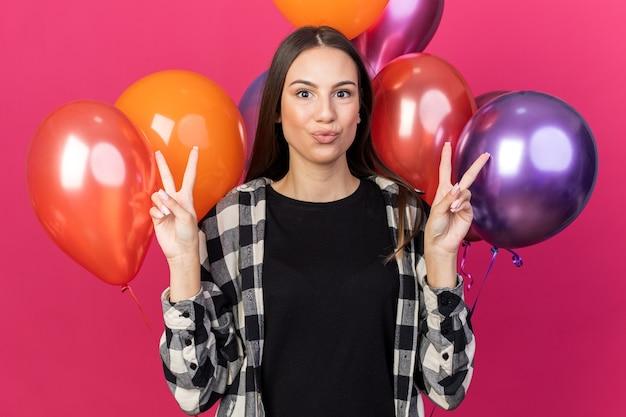 Erfreut junges schönes mädchen, das vor ballons steht und friedensgeste zeigt, isoliert auf rosa wand