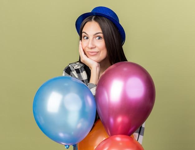 Erfreut junges schönes mädchen mit blauem hut, das hinter ballons steht und die hand auf die wange legt