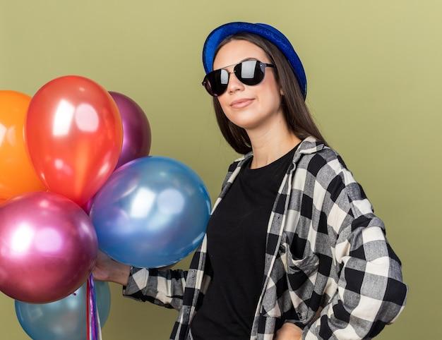 Erfreut junges schönes mädchen mit blauem hut mit brille, die luftballons hält, die hand auf die hüfte legt