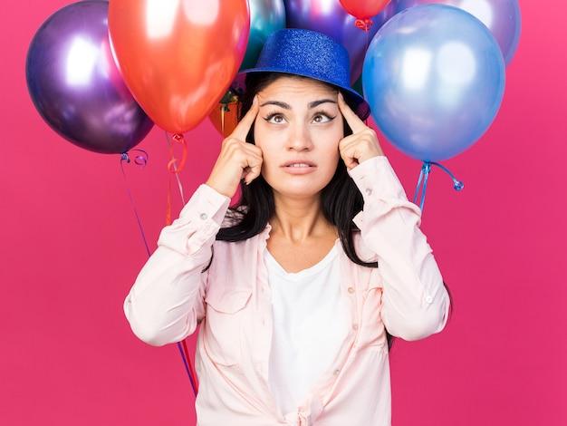 Erfreut junges schönes mädchen mit partyhut, das vor ballons steht und finger auf die augen legt, isoliert auf rosa wand