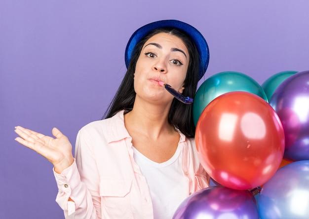 Erfreut junges schönes mädchen mit partyhut, der luftballons hält, die partypfeife bläst, die hand ausbreitet