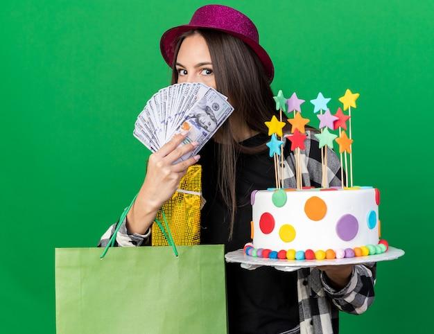 Erfreut junges schönes mädchen mit partyhut hält kuchen mit geschenktüte bedeckt gesicht mit bargeld