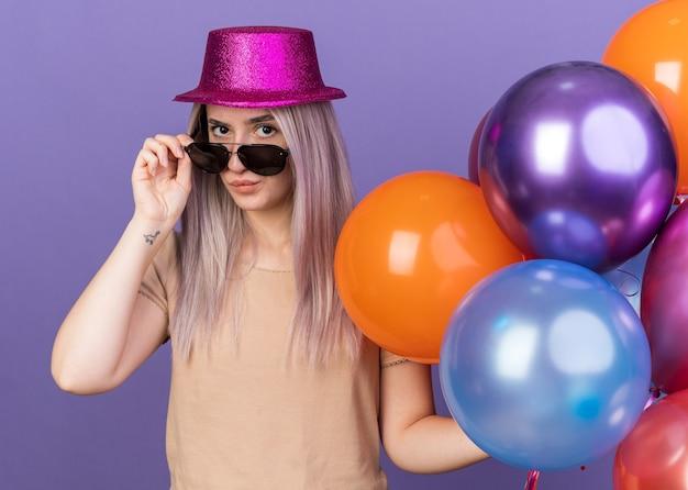 Erfreut junges schönes mädchen mit partyhut mit brille mit ballons