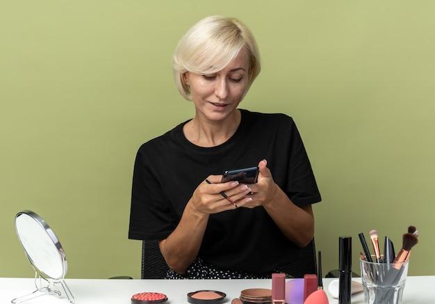 Erfreut junges schönes mädchen sitzt am tisch mit make-up-tools, die das telefon in der hand halten und betrachten, isoliert auf olivgrüner wand