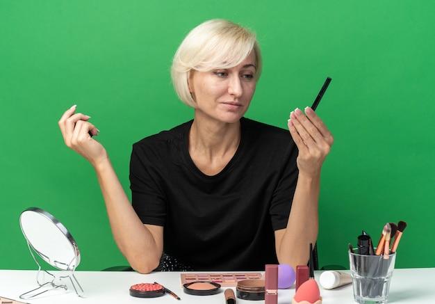Erfreut junges schönes mädchen sitzt am tisch mit make-up-tools, die eyeliner auf grüner wand isoliert halten