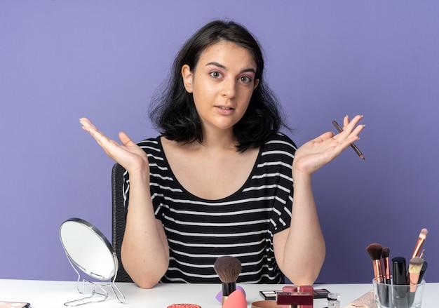Erfreut junges schönes mädchen sitzt am tisch mit make-up-tools, die eyeliner halten, die hände isoliert auf blauer wand ausbreiten
