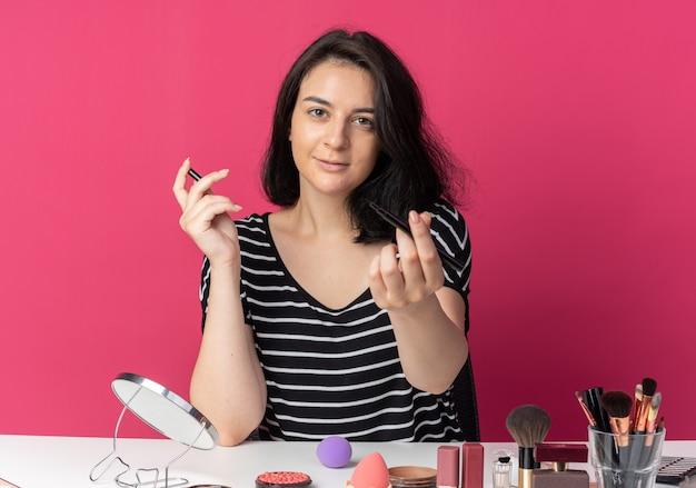 Erfreut junges schönes mädchen sitzt am tisch mit make-up-tools, die eyeliner isoliert auf rosa wand halten