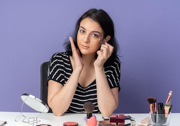 Erfreut junges schönes mädchen sitzt am tisch mit make-up-tools ziehen pfeil mit eyeliner isoliert auf blauer wand