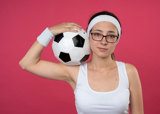 Erfreut junges sportliches mädchen in optischer brille mit stirnband und armbändern hält ball auf der schulter