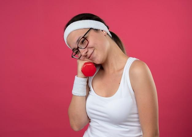 Erfreut junges sportliches mädchen in optischer brille mit stirnband und armbändern hält und legt gesicht auf hantel