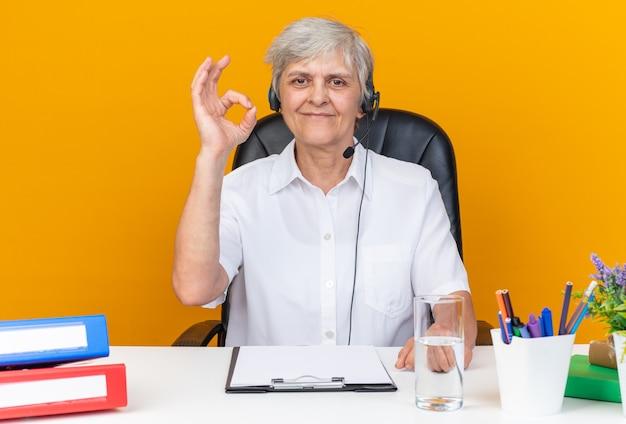 Erfreut kaukasische callcenter-betreiberin auf kopfhörern, die am schreibtisch mit bürowerkzeugen sitzen und ein ok-zeichen gestikulieren