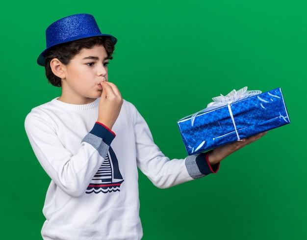 Erfreut kleiner junge mit blauem partyhut, der eine geschenkbox mit köstlicher geste hält und betrachtet