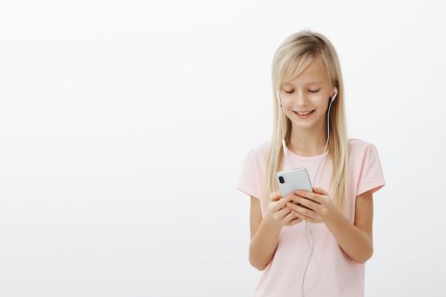 Erfreut kreatives kind, das videos sieht, während es auf mutter wartet. porträt des entzückenden jungen mädchens mit hellem haar, das musik in den kopfhörern hört und smartphone hält, das von der positiven nachricht lächelt