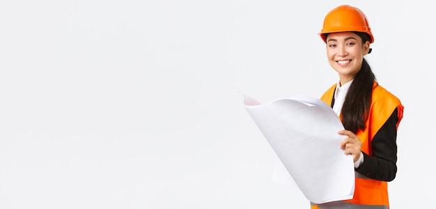 Erfreut lächelnde asiatische bauleiterin, die bauplänen während des hausbaus folgt, zufrieden in die kamera schaut, den architektenplan studiert, weißen hintergrund im schutzhelm steht