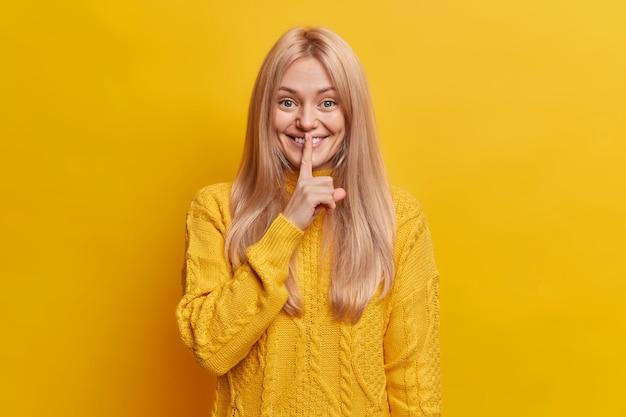 Erfreut lächelnde blonde frau macht geheime geste, finger auf der lippe, still
