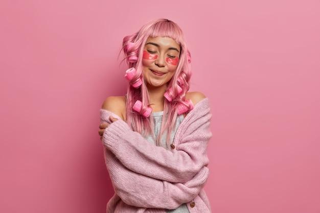 Erfreut lächelnde charmante dame schließt die augen und umarmt sich, fühlt sich in einem neuen strickpullover wohl, trägt beauty-pads und lockenwickler auf langen rosa haaren auf