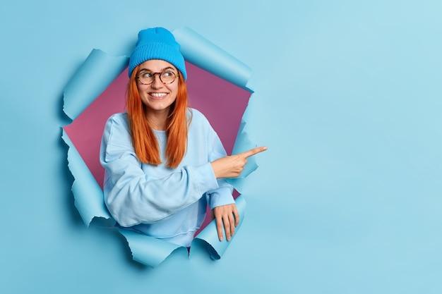Erfreut lächelnde rothaarige frau zeigt finger auf kopie raum zeigt sonderangebot oder einkaufsverkauf empfiehlt guten rabatt in stilvollen blauen outfit gekleidet hat fröhliche stimmung bricht durch papierloch