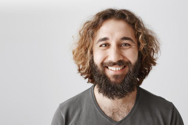 Erfreut lächelnder mann aus dem nahen osten, der glücklich und entzückt aussieht