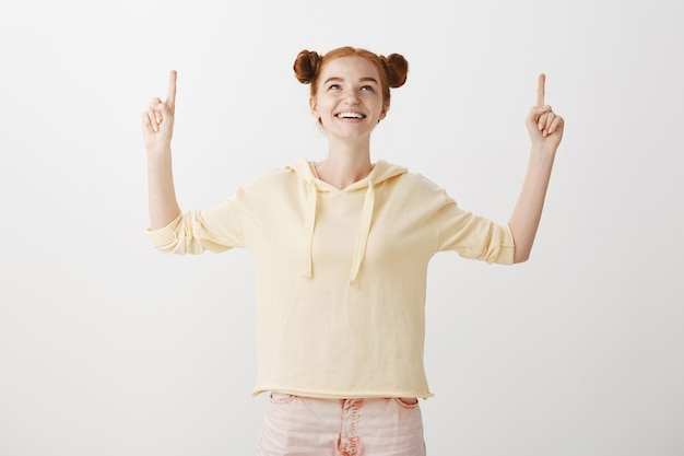 Erfreut lächelndes rothaariges mädchen, das finger nach oben zeigt