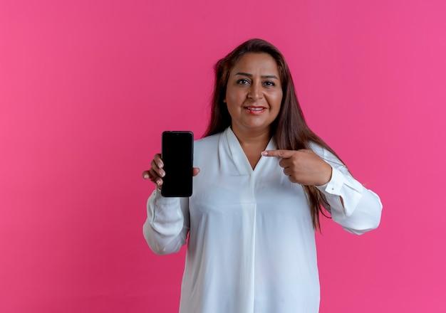 Erfreut lässige kaukasische frau mittleren alters halten und zeigt auf telefon