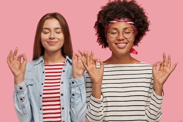 Erfreut machen zwei frauen unterschiedlicher rasse mit beiden händen eine gute geste, schließen die augen und versuchen sich zu konzentrieren