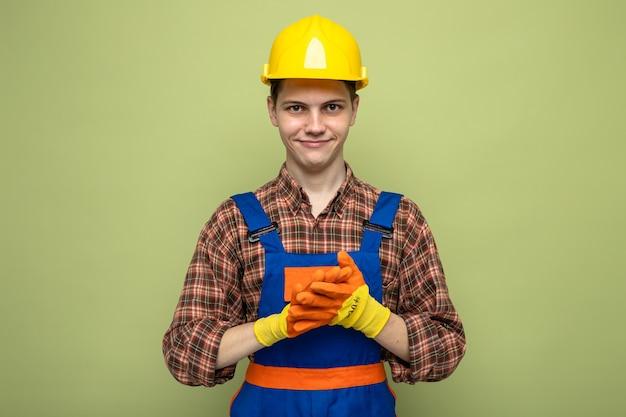 Erfreut mit den händen zusammen junger männlicher baumeister, der uniform mit handschuhen trägt