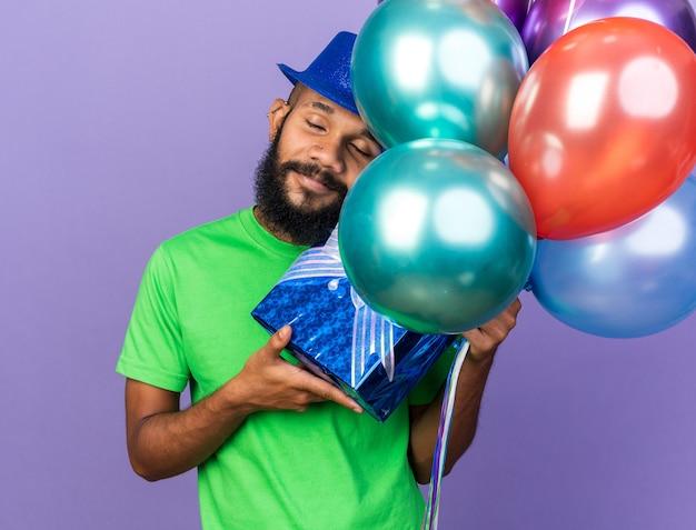 Erfreut mit geschlossenen augen, die den kopf kippen, junger afroamerikanischer mann mit partyhut, der luftballons mit geschenkbox hält