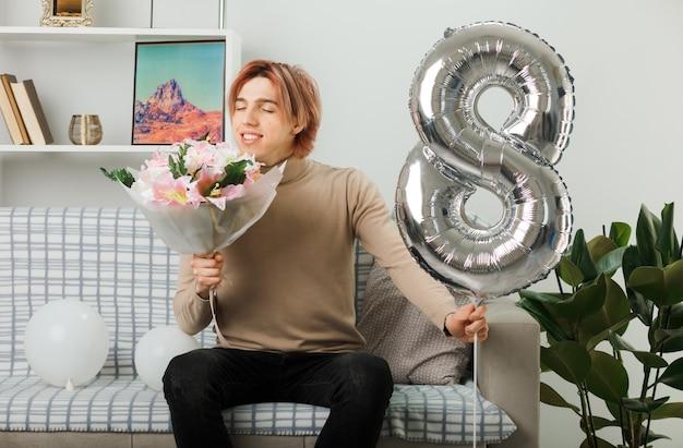 Erfreut mit geschlossenen augen, hübscher kerl am glücklichen frauentag, der den ballon nummer acht hält und blumenstrauß in der hand schnüffelt, der auf dem sofa im wohnzimmer sitzt