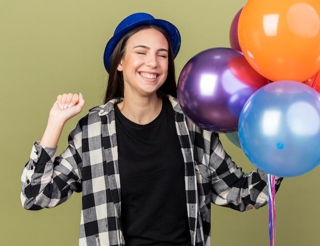 Erfreut mit geschlossenen augen, junge schöne frau mit blauem hut, die luftballons hält, die ja-geste einzeln auf olivgrüner wand zeigen?