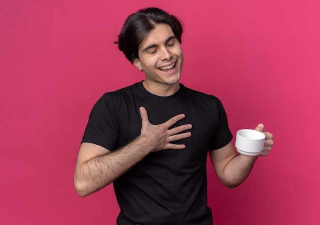 Erfreut mit geschlossenen augen junger gutaussehender kerl mit schwarzem t-shirt mit tasse kaffee isoliert auf rosa wand on
