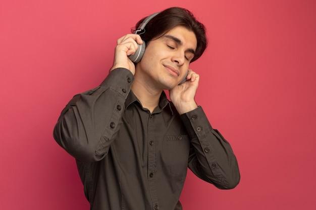 Erfreut mit geschlossenen augen junger hübscher kerl, der schwarzes t-shirt mit kopfhörern trägt, hören musik isoliert auf rosa wand