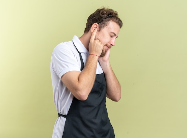 Erfreut mit geschlossenen augen junger männlicher friseur, der uniform bedeckte ohren mit fingern trägt, die auf olivgrüner wand isoliert sind