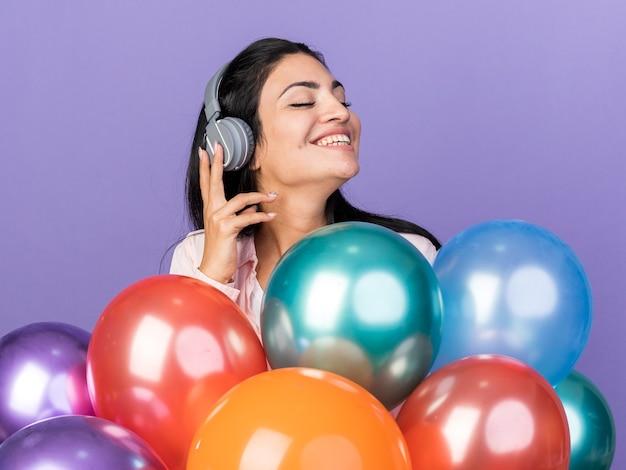 Erfreut mit geschlossenen augen junges schönes mädchen mit kopfhörern, die hinter luftballons stehen