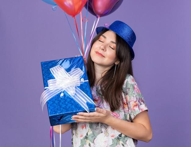 Erfreut mit geschlossenen augen junges schönes mädchen mit partyhut mit luftballons mit geschenkbox isoliert auf blauer wand